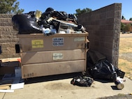 Environmental specialists with the 60th Civil Engineer Squadron at Travis Air Force Base, California, found cans of paint, a microwave oven and other hazardous materials in a dumpster behind the base legal office in July 2017. Courtesy photo/ Anthony Llanes.