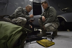 Tech Sgt. Brian Duell, left, 437th Aircraft Maintenance Squadron aerospace maintenance craftsman, and Airman 1st Class Nicolas Rainey, right, 437th AMXS aerospace maintenance technician, perform ground maintenance on a C-17 Globemaster III in preparation for a Joint Forcible Entry training event in support of the U.S. Air Force Weapons School Integration phase Dec. 8. Thirty seven C-17s, 21 C-130 Hercules and 120 U.S. Army paratroopers participated in the mobility portion of the WSINT phase during a simulated mass JFE event over a contested target Dec. 9, on a range near Nellis Air Force Base, Nev. The event demonstrates the U.S. Air Force's ability to execute rapid, decisive responses to crises worldwide.