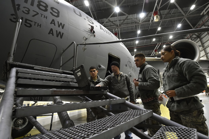 Members of the 437th Aircraft Maintenance Squadron perform ground maintenance on a C-17 Globemaster in preparation for a Joint Forcible Entry training event in support of the U.S. Air Force Weapons School Integration phase Dec. 8. Thirty seven C-17s, 21 C-130 Hercules and 120 U.S. Army paratroopers participated in the mobility portion of the WSINT phase during a simulated mass JFE event over a contested target Dec. 9, on a range near Nellis Air Force Base, Nev. The event demonstrates the U.S. Air Force's ability to execute rapid, decisive responses to crises worldwide.