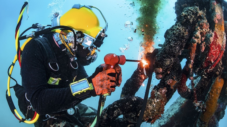 A cuts uses a tool with a flame to cut a section of metal underwater.
