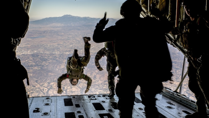 A Marine jumps out of the back of an aircraft, as two others prepare to do the same.