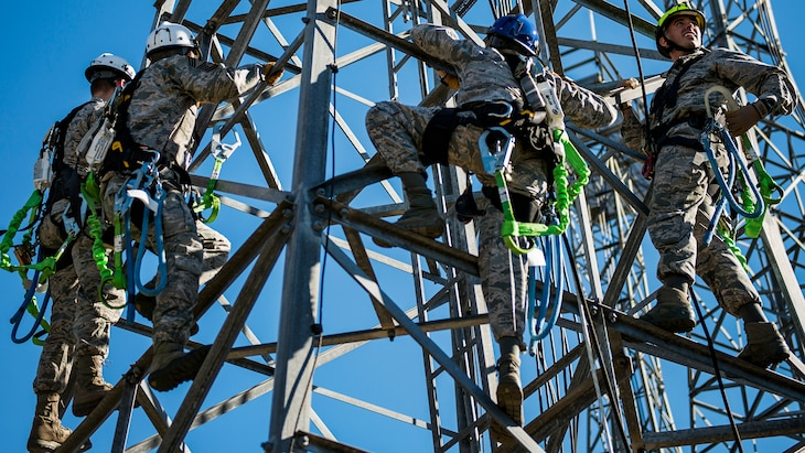 Several airmen with climbing gear stand on a tower.