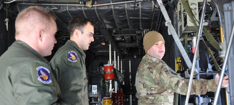 Tech. Sgt. Michael Hoffman, right, a C-130H loadmaster with the 700th Airlift Squadron, Dobbins, Air Reserve Base, Georgia, teaches Senior Airmen Erik Hannigan, left, and Kevin Pajor, C-130 loadmasters from the 96th Airlift Squadron, Minneapolis-St. Paul Air Reserve Station, Minnesota, about the towed parachute retrieval system during the loadmaster refresher course, Nov. 18 at Peterson Air Force Base, Colorado. About 70 loadmasters attended the training hosted by the 302nd Airlift Wing. (U.S. Air Force photo/Daniel Butterfield)