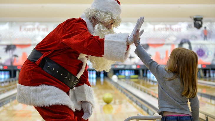 A man dressed as Santa Claus high-fives a girl in a bowling alley.