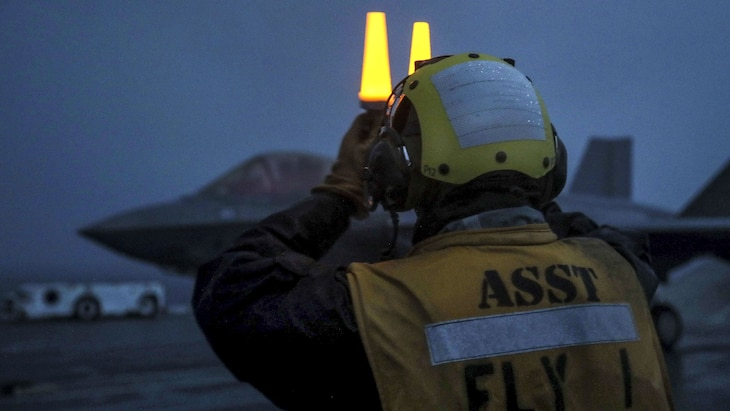 A sailor holds two yellow lights above his face on a ship's flight deck, with an jet in the background.