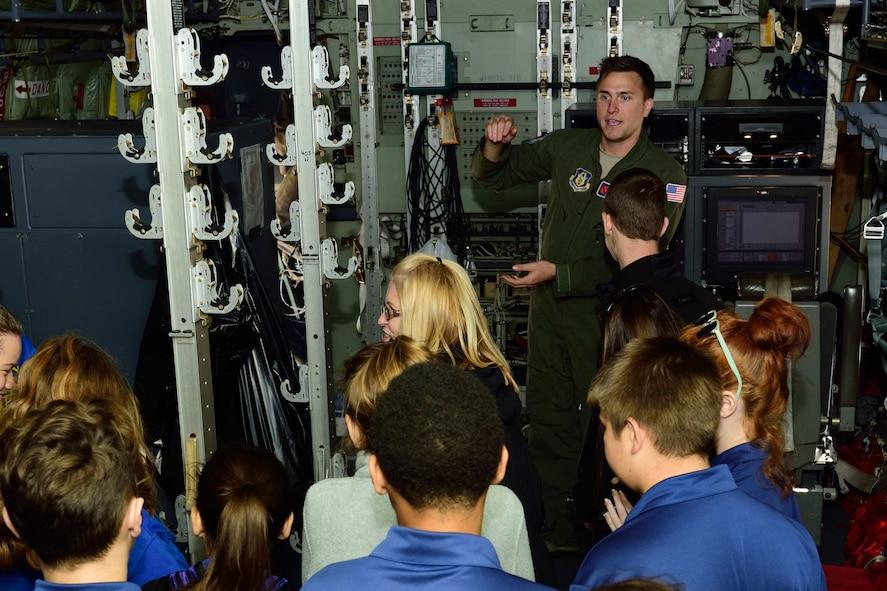 """Staff Sgt. Nathan Calloway, 53rd Weather Reconnaissance Squadron weather reconnaissance loadmaster, talks about the 53rd WRS """"Hurricane Hunters"""" mission to students and teachers from Courtney Christian School out of Hammond, Alabama, Dec. 12, 2017, at Keesler Air Force Base, Mississippi. The school group toured one of the squadron's WC-130J Super Hercules aircraft and visited the 41st Aerial Port Squadron to learn about how they support the flying missions of the 53rd WRS and the 815th Airlift Squadron. (U.S. Air Force photo by Tech. Sgt. Ryan Labadens)"""