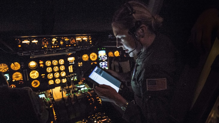 A pilot in a dark cockpit with uillum looks at a screen.
