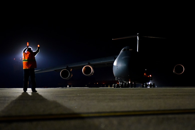 Eddie Holmes, 4th Equipment Maintenance Squadron transit alert aircraft servicer, marshals a taxiing C-5M Super Galaxy, Sept. 29, 2017, at Seymour Johnson Air Force Base, North Carolina. The Super Galaxy is assigned to Dover Air Force Base, Delaware. (U.S. Air Force photo by Airman 1st Class Victoria Boyton)