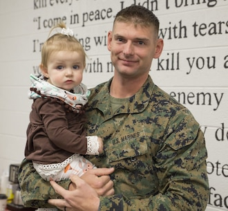 Staff Sgt. Christopher D'arcy, platoon sergeant, 2nd platoon, Charlie Co., Fleet Anti-terrorism Security Team, U.S. Marine Corps Security Forces Regiment, holds his daughter Caroline, 1, during a welcome home ceremony aboard Camp Allen, Va. Dec. 11. FAST Marines deployed for 6 months in Europe conducting security operations. (Official U.S. Marine Corps photo by Chris Jones/Released)
