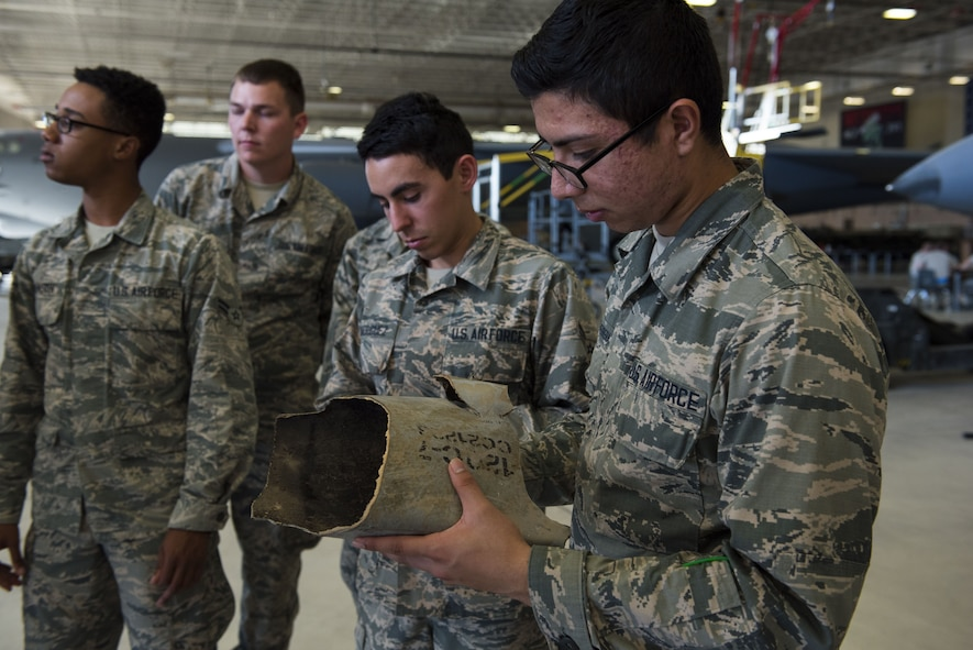 Airman holds a piece of shrapnel from an advanced medium-range air-to-air missile.