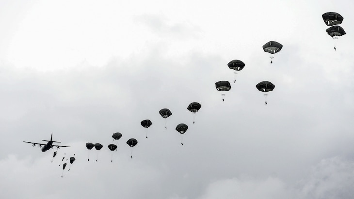 Paratroopers jump from an aircraft during overcast conditions.