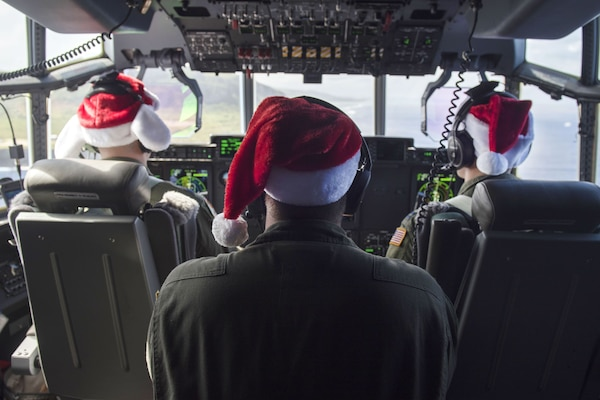 Air Force pilots and a crew chief fly a C-130J Super Hercules over Andersen Air Force Base