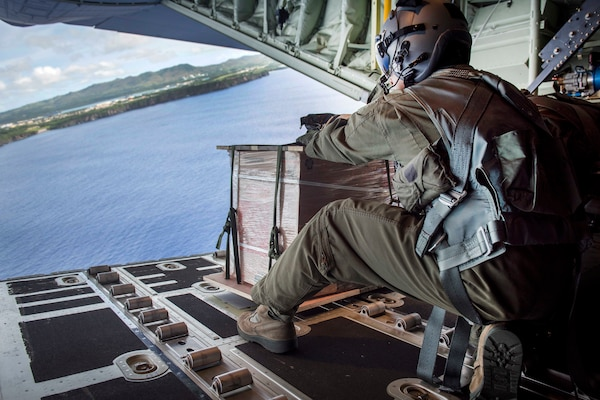 Air Force Staff Sgt. Jojie Arcega pushes a practice bundle out from a C-130J Super Hercules aircraft.