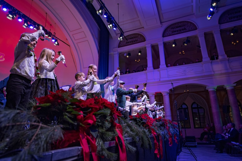 Children ring bells on stage during a United States Air Forces in Europe Band Christmas concert at Fruchthalle in Kaiserslautern, Germany, Dec. 8, 2017. The children rang the bells while the USAFE Band played Christmas music for local community members. (U.S. Air Force photo by Senior Airman Devin Boyer)