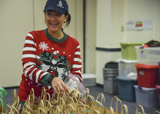 Jean Morris, spouse of Maj. Gen. Shaun Q. Morris, Air Force Nuclear Weapon Center commander, bags cookies during the Kirtland Spouse's cookie drive at Kirtland Air Force Base, N.M., Dec. 12. The cookie drive's purpose is to raise morale for Airmen, as many of them are spending the holidays away from their families.