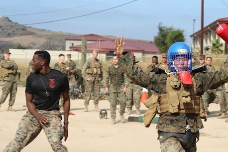 1stLt Oshiro walks away victorious after Sgt Rawlins declares him the winner during pugil sticks. The Marines of 9th Communication Battalion competed in a variety of MCMAP contests to include pugil sticks and ground fighting following a 6 mile gas hike.