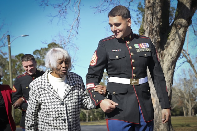 A Marine escorts a guest in to the 48th annual Senior Tea aboard Marine Corps Air Station Beaufort, Dec. 11. The time honored event began in 1968. Since then the event has been held to honor one of Team Beaufort's greatest generations. The Marine is stationed aboard MCAS Beaufort.