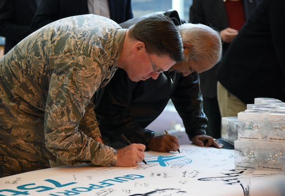 Col. C. Mike Smith, 81st Training Wing vice commander, signs a banner during the Gulfport-Biloxi International Airport 75 Year Commemoration Dec. 13, in Gulfport, Mississippi. A historical marker at the entrance of the airport was unveiled by local dignitaries during the event honoring the airport's ties to the military dating back to 1942. The U.S. Air Force Band of the West, Nightwatch, also performed during the event. (U.S. Air Force photo by Kemberly Groue)