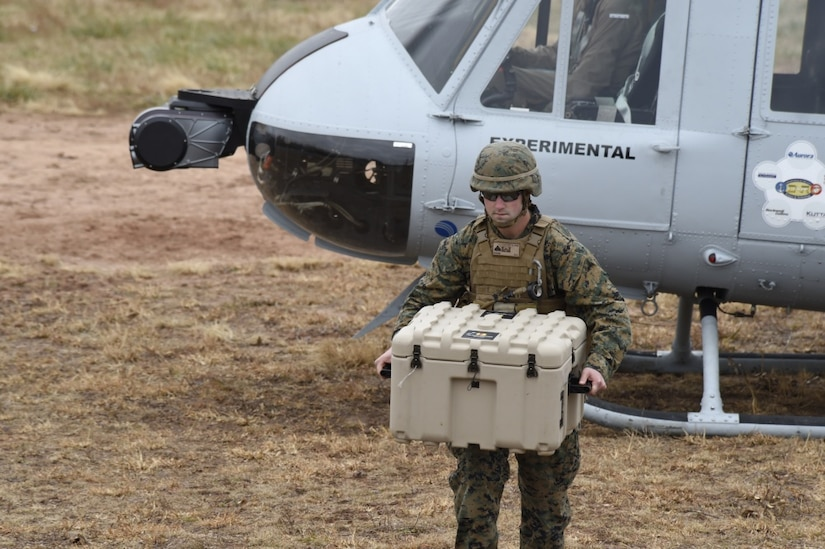 A Marine offloads cargo from a UH-1 Huey helicopter equipped with an Office of Naval Research-sponsored Autonomous Aerial Cargo/Utility System autonomy kit following a landing during final testing at Marine Corps Base Quantico, Va.