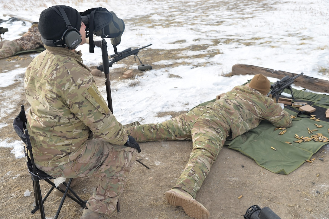 Senior Airman Richard Corpus-Munoz, 341st Security Support Squadron tactical response force nuclear advanced designated marksman flight trainer, left, spots for Airman 1st Class Keanu Valle, 341st SSPTS TRF NADM, while he fires a M24 sniper rifle Dec. 12, 2017, at Fort Harrison, Mont.
