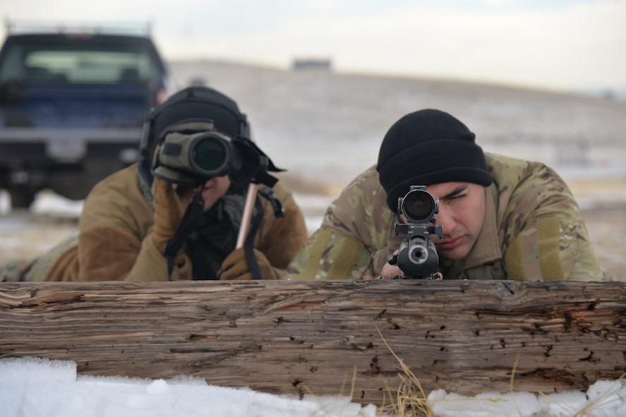 Airman 1st Class Keanu Valle, 341st Security Support Squadron tactical response force nuclear advanced designated marksman, left, and Senior Airman Richard Corpus-Munoz, 341st SSPTS TRF NADM flight trainer, pose for a photo Dec. 12, 2017, at Fort Harrison, Mont.