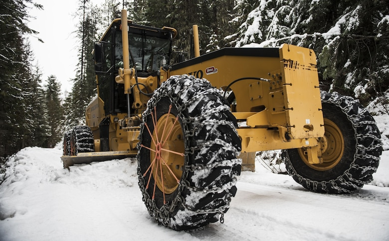 "Tech. Sgt. Kyle Hiener, 336th Training Support Squadron field's operations NCO in-charge, operates a motor-grader to remove snow from roads in the Air Force Survival School Training Area in Cusick, Washington, Dec. 7, 2017. These Airmen are known throughout the Air Force as Civil Engineer ""Dirt Boys,"" but when they're a part of the 336th Training Support Squadron, they're called ""Road Runners."" The Road Runners operate various vehicles to clear back roads in the National Forest, to include: motor graders, loaders, bulldozers and dump trucks. (U.S. Air Force photo/Senior Airman Sean Campbell)"