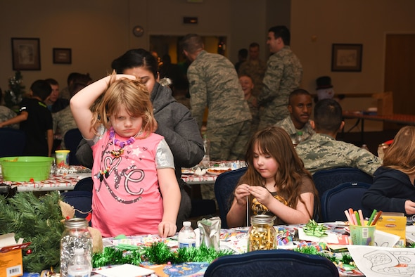A child has her arts and crafts necklace tied on during Operation Provide Joy at F.E. Warren Air Force Base, Wyo., on Dec. 9, 2017. The event was a joint effort between the 321st Missile Squadron and the Salvation Army. The event was established to booster community partnership and to help local families in need get their children into the holiday spirit. (U.S. Air Force photo by Airman 1st Class Abbigayle Wagner)