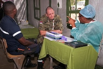 Lt. Col. Alexandar Spasic (center), urologist with the Serbian Armed Forces, consults with a member of the Angolan Armed Forces in one of the clinics in the village of Vale do Paraiso during the PAMBALA 2017 medical exercise Dec. 11, 2017, in Bengo, Angola, Dec. 11, 2017. PAMBALA is the first-ever trilateral combined medical engagement to take place in the Republic of Angola, highlighted by a four-day clinical operations mission focusing on services like preventative medicine, pediatrics, family practice, dermatology, optometry, dentistry, and obstetrics and gynecology at various field hospitals in the province. The historic engagement aims to build the foundation for future engagements between the U.S. and Angola, as well as enhance the 11-year partnership the Ohio National Guard maintains with Serbia, through the National Guard State Partnership Program. (Ohio National Guard photo by Staff Sgt. Wendy Kuhn)