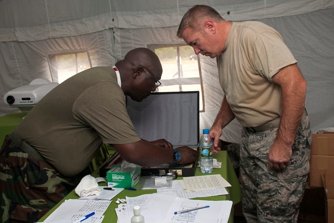 Tech. Sgt. William McConaha (right), an Ohio Air National Guard ophthalmology technician, reviews paperwork alongside a member of the Angolan Armed Forces in the ophthalmology clinic in the village of Vale do Paraiso during the PAMBALA 2017 medical exercise Dec. 12, 2017, in Bengo Province, Angola. The purpose of the engagement for the Ohio National Guard is to give personnel the opportunity to share best practices, strengthen medical treatment processes, establish new relationships with members of the Angolan Armed Forces and to nurture their existing 11-year partnership with Serbia, through the National Guard State Partnership Program. (Ohio National Guard photo by Staff Sgt. Wendy Kuhn)