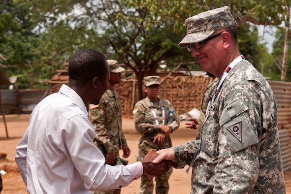 Maj. Marshal Bickert, a preventative medicine officer with the Ohio Army National Guard, shakes hands with the school administrator in the village of Vale do Paraiso during the PAMBALA 2017 medical exercise Dec. 12, 2017, in Bengo, Angola. The goal of the engagement for the Ohio National Guard is to give personnel the opportunity to share best practices, strengthen medical treatment processes, establish new relationships with members of the Angolan Armed Forces and to nurture the ONG's existing 11-year partnership with the Republic of Serbia, through the National Guard State Partnership Program. (Ohio National Guard photo by Staff Sgt. Wendy Kuhn)