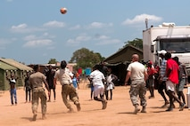 Members of the Ohio National Guard play soccer with children in the village of Vale do Paraiso during the PAMBALA 2017 medical exercise Dec. 12, 2017, in Bengo Province, Angola. PAMBALA is the first-ever trilateral combined medical engagement to take place in the Republic of Angola, and consist of a four-day clinical operations mission focusing on services like preventative medicine, pediatrics, family practice, dermatology, optometry, dentistry, and obstetrics and gynecology at various field hospitals in the province. The engagement aims to build the foundation for future engagements between the U.S. and Angola, and enhance the 11-year partnership the Ohio National Guard has with the Republic of Serbia through the National Guard State Partnership Program. (Ohio National Guard photo by Staff Sgt. Wendy Kuhn)