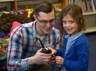 "U.S. Air Force Airman 1st Class Roy Smith, 100th Communications Squadron radio frequency transmissions systems technician, shows a student at Beck Row Primary Academy how to use a radio to talk to Santa, Dec. 12, 2017. More than 100 pupils, aged 4 to 7 had the chance to participate in the ""Radio Santa"" program. (U.S. Air Force photo by Airman 1st Class Benjamin Cooper)"