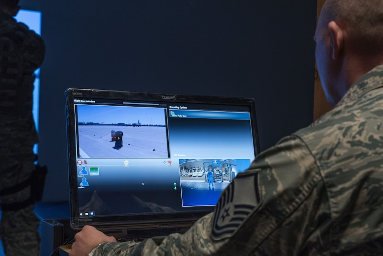 Master Sgt. Theodore Hemmah, a training manager for the 934th Security Forces Squadron, monitors fire team members as they participate in a scenario on the Multiple Interactive Learning Objectives simulator at the Minneapolis-St. Paul Air Reserve Station, Minn. on Dec. 14, 2017. The system includes software that allows instructors to create fully interactive video scenarios suited to their local missions. (U.S. Air Force photo by Master Sgt. Eric Amidon)