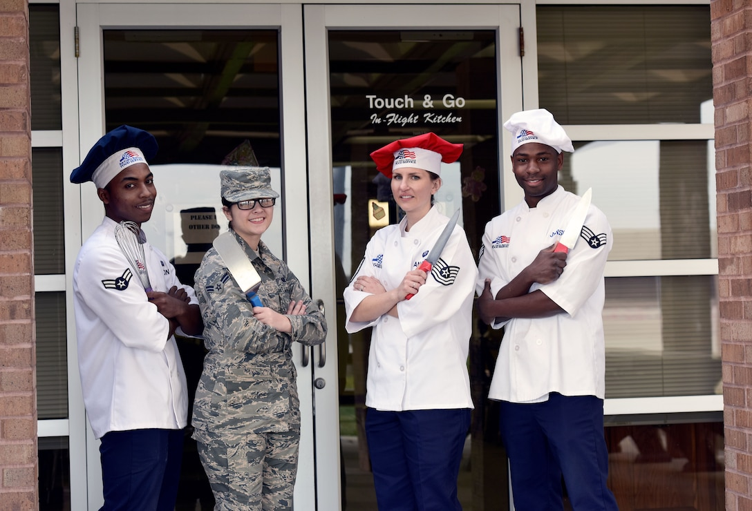 """From left to right, Airman 1st Class Mrqkze Macon, Airman 1st Class Shelby Carson, Tech. Sgt. Jessica Ancheta, and Senior Airman Demarcus Johnson, all Airmen assigned to the 509th Force Support Squadron, stand outside of the """"Touch & Go"""" kitchen on the flightline at Whiteman Air Force Base, Mo., Dec. 11, 2017."""