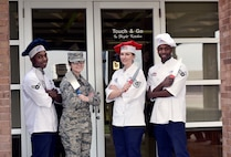"From left to right, Airman 1st Class Mrqkze Macon, Airman 1st Class Shelby Carson, Tech. Sgt. Jessica Ancheta, and Senior Airman Demarcus Johnson, all Airmen assigned to the 509th Force Support Squadron, stand outside of the ""Touch & Go"" kitchen on the flightline at Whiteman Air Force Base, Mo., Dec. 11, 2017."