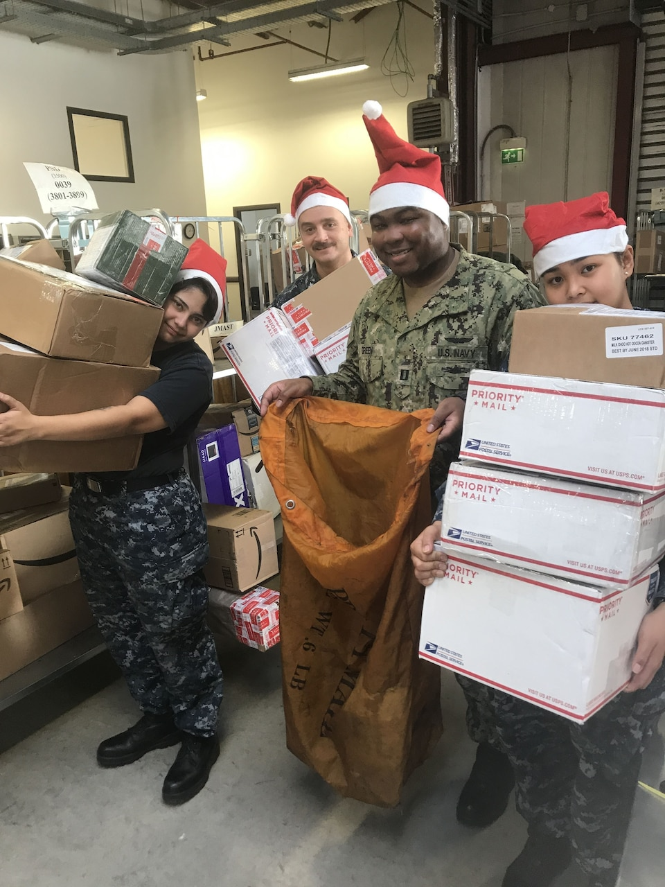 Navy Lt. Joseph Green, director of the fleet mail center in Sigonella, Italy, and sailors assigned to the center hold a small sample of the mail that flows through on its way to deployed units operating in the Mediterranean and tenant commands at Naval Air Station Sigonella.