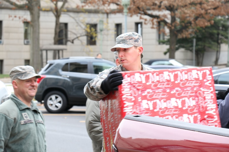 During the 2017 Holiday Wish Program, 193rd Regional Support Group Airmen and Pennsylvania Army Guardsmen carry in donated gifts into the Keystone Building, Harrisburg, Pennsylvania, Dec. 6, 2017. After a ceremony, with the help of volunteer state employees, they loaded the gifts into military vehicles and delivered them to participating county assistance offices for distribution to families and individuals.  (U.S. Air National Guard photo by Master Sgt. Culeen Shaffer/Released)