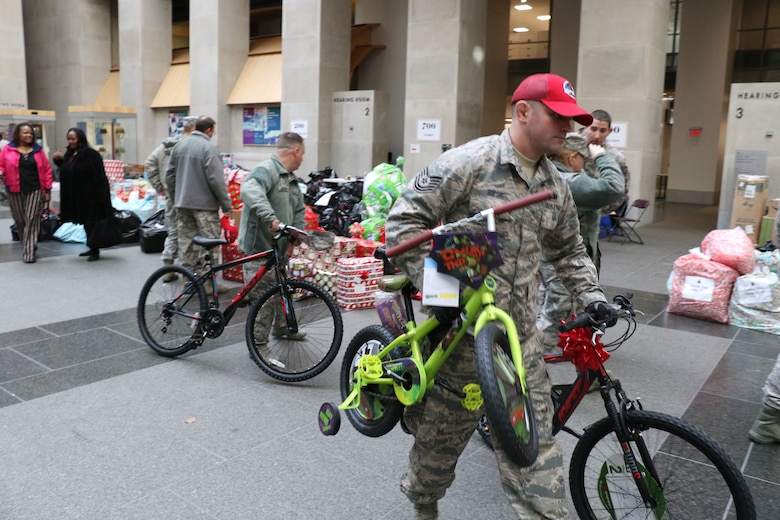 As part of the 28th annual Holiday Wish Program, 193rd Regional Support Group Airmen and Pennsylvania Army Guardsmen with the help of volunteer state employees, load donated gifts into military vehicles at the Keystone Building, Harrisburg, Pennsylvania, Dec. 6, 2017. The donated gifts were delivered to participating county assistance offices for distribution to families and individuals.  (U.S. Air National Guard photo by Master Sgt. Culeen Shaffer/Released)