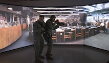 Staff Sgt. Tyler Frats, left, and Staff Sgt. Brian Walker, both from the 821st Security Forces Squadron, demonstrate an active shooter drill using a combat simulator at Thule Air Base, Greenland, Dec. 11, 2017 . With the base being so remote, the simulator allows for the Airmen to train regardless of the weather. (U.S. Air Force photo by Senior Airman Dennis Hoffman)