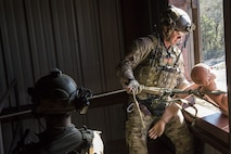 Pararescuemen from the 38th Rescue Squadron (RQS) propel a mannequin out of a window during a full mission profile exercise, Dec. 12, 2017, at Moody Air Force Base, Ga. During the training, the 38th RQS recovered victims while under enemy fire to prepare for future search and rescue missions and to assess their unit's ability to work cohesively to accomplish the mission. (U.S. Air Force photo by Airman Eugene Oliver)