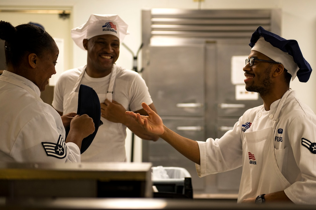 Staff Sgt. Latoya Wells, left, 23d Force Support Squadron (FSS) food services supervisor, Senior Airman Cameron Morrow, middle, 23d FSS food services journeyman, and Airman 1st Class Keven Fears, 23d FSS food services specialist, share a laugh in the Georgia Pines Dining Facility (DFAC), Dec. 12, 2017, at Moody Air Force Base, Ga. Through teamwork, adaption and striving for excellence, the Georgia Pines DFAC Airmen are able to ensure Team Moody is fed and ready to finish the fight. (U.S. Air Force Base photo by Airman 1st Class Erick Requadt)