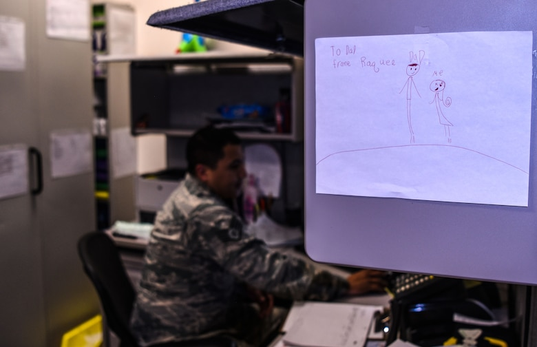 Staff Sgt. Miguel Guajardo, 90th Medical Group NCO in charge of logistics, works in his office in the dental clinic with a drawing from his child on the wall at F.E. Warren Air Force Base, Wyo., on Dec. 13, 2017. Miguel works with his wife in the clinic and they are proving it is possible to be successful together at home and work. Success for this couple means putting family first.
