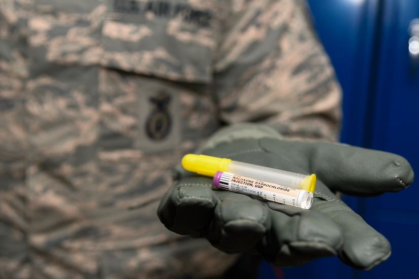 Staff Sergeant Matthew Pick, 66th Security Forces Squadron, holds a nasal applicator and naloxone medication vial.