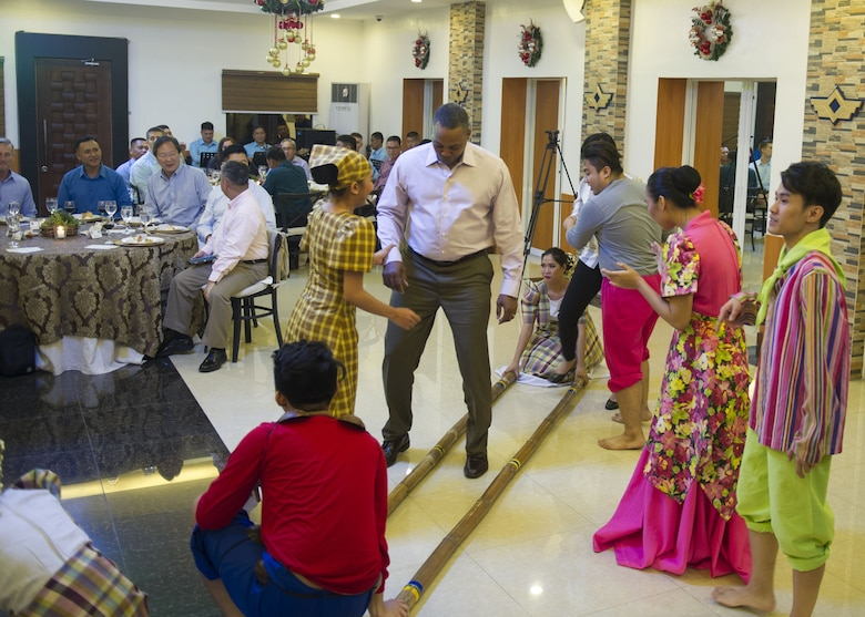 Chief Master Sgt. Anthony Johnson, Pacific Air Forces command chief, learns a traditional Filipino dance during a dinner hosted by the PAF, Manila, Philippines Dec. 11.