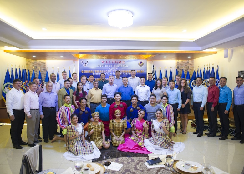 Gen. Terrence J. O'Shaughnessy, Pacific Air Forces commander, Lt. Gen. Galileo Gerard Kintanar, Philippine Air Force commanding general, Chief Master Sgt. Anthony Johnson, PACAF command chief, and staffs pose for a group photo with the cultural performers following a dinner hosted by the PAF, Manila, Philippines Dec. 11.