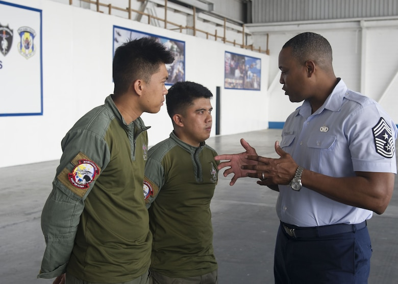 Chief Master Sgt. Anthony Johnson, Pacific Air Forces command chief, speaks with Philippines Air Force crew chief during a visit to Clark Air Base, Philippines Dec. 12
