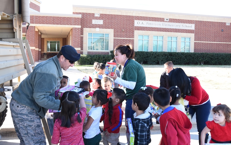 Tech. Sgt. Chad Ragland, a 301st Security Forces Squadron member, collects toys from local elementary students Friday, Dec. 15, 2017, during the unit's annual Ruck for Kids drive. The toys are for kids who are hospitalized at Cook Children's Medical Center in Fort Worth, Texas. Students from O.A. Peterson, Haslet, and Sendera Ranch Elementary schools participated in the drive. (U.S. Air Force photos by Tech. Sgt. Melissa Harvey)