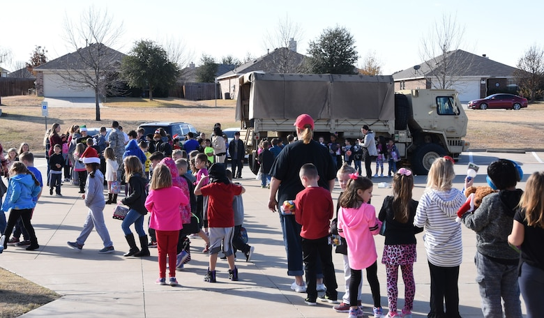 Members of the 301st Security Forces Squadron collect toys from Sendera Ranch Elementary students in Haslet, Texas, Friday, Dec. 15, 2017, during their annual Ruck for Kids drive. The toys are for kids who are hospitalized at Cook Children's Medical Center in Fort Worth, Texas. Students from O.A. Peterson, Haslet, and Sendera Ranch Elementary schools participated in the drive. (U.S. Air Force photos by Tech. Sgt. Melissa Harvey)
