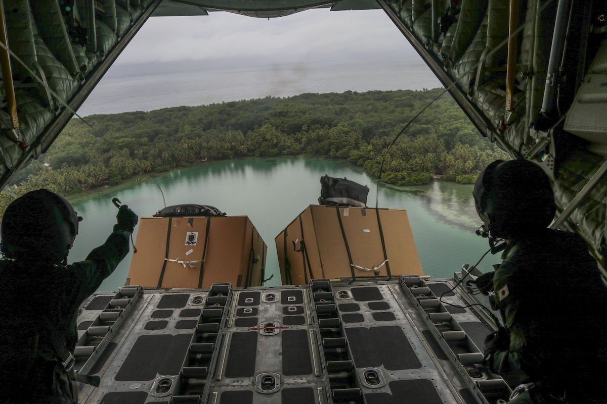 Troops drop food, supplies and educational materials from a C-130.