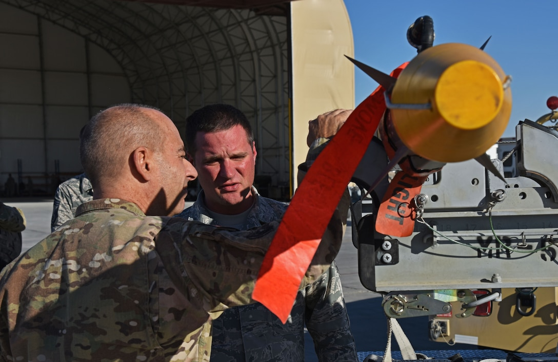 U.S. Air Force Lt. Gen. Jeffery Harrigian, U.S. Air Forces Central Command Commander, talks with Master. Sgt. Robert Brown, 100th Expeditionary Fighter Squadron Munitions Production superintendent, at the 407th Air Expeditionary Group in Southwest Asia, Dec. 14, 2017. Brown talked about the F-16 Fight Falcon's weapon systems and the capability of the missile. (U.S. Air Force photo by Staff Sgt. Joshua Edwards/Released)